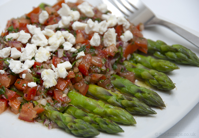 Asparagus with tomato salsa and crumbled cheese